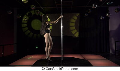 Young woman pole dancer performing sensual dance on lighted stage at night club