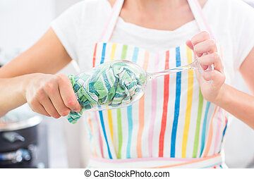 Young woman polishing a glass in her modern kitchen