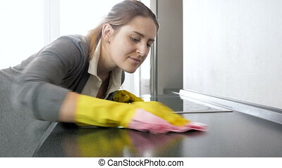 Young woman polishing and cleaning kitchen countertop