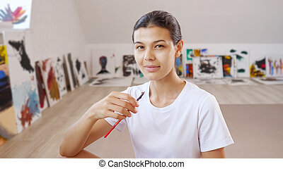 young woman poses smiling against own paintings at walls