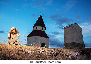 Young woman posing by the church on the hill