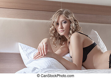 young woman posing in evening bed