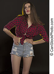 Young woman posing in jeans shorts, red checked shirt