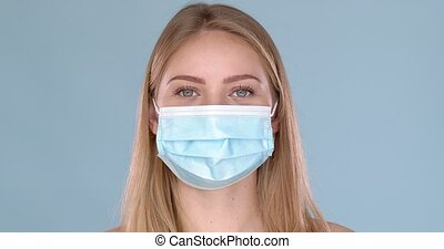 Young woman posing in medical face mask. Looking at camera with smile behind