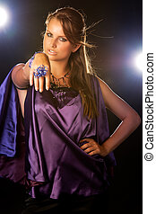 young woman posing in purple dress, studio shot with lights in background