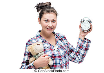 Young woman posing in studio on a white background in pajamas with objects in hands