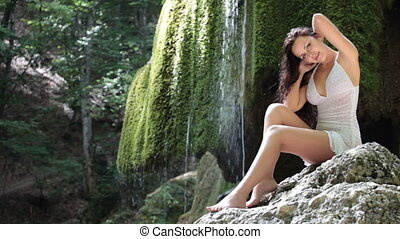 young woman posing near a mountain waterfall in the summer woods looking at the camera smiling