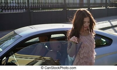 Young woman posing near luxury sports car in a city