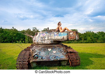 Young woman posing on army tank.