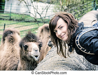 Young woman posing with camel, blue filter