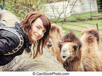 Young woman posing with camel, yellow filter