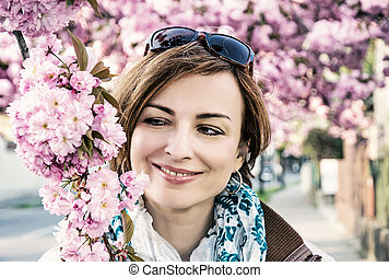 Young woman posing with flowering sakura tree, blue filter