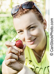 Young woman posing with fresh strawberry, spring garden theme