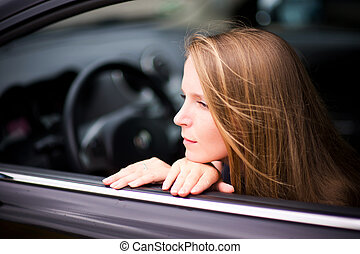 young woman posing with hands on the window line in a car on a summer day