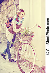 Young woman posing with retro bicycle with wicker baskets, beauty photo filter