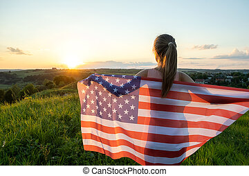 Young woman posing with USA national flag outdoors at sunset. Positive girl celebrating United States independence day.