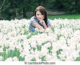 Young woman posing with white daffodils, blue filter