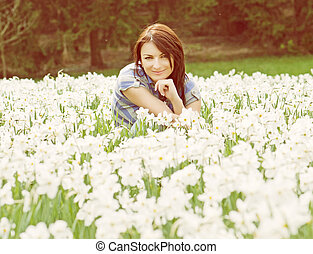 Young woman posing with white daffodils, yellow photo filter