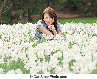 Young woman posing with white daffodils