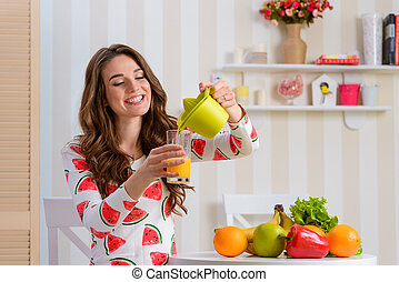 Young woman pouring juice into a glass from a juicer