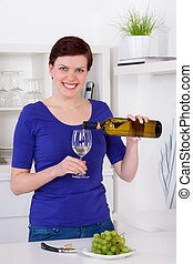 young woman pouring white wine in a glass in her kitchen