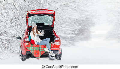 Young woman pours a hot drink, coffee, cocoa or tea from a thermos while sitting in the trunk of a red car on the background of a winter forest