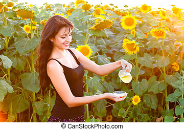 young woman pours sunflower oil from  jug into a bowl
