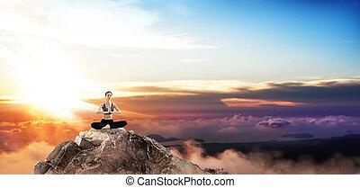Young woman practice yoga on mountain peak cliff.