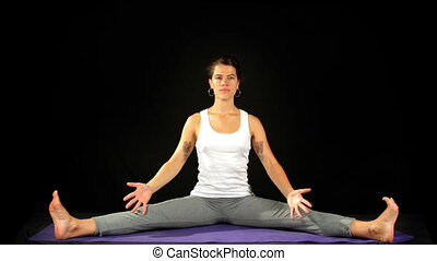 young woman practices yoga moves and positions