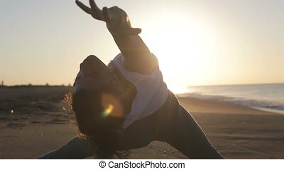 young woman practices yoga on a beach at sunrise