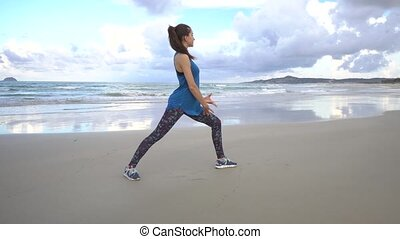 Young woman practices yoga on a beach at sunrise in front of sea. Morning gymnastic.