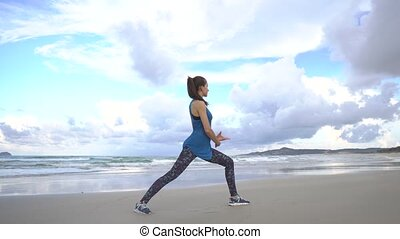 Young woman practices yoga on a beach at sunrise in front of sea. Morning gymnastic. Rise hands.