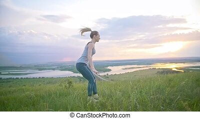 Young woman practicing acrobatic flip through the sun at sunset