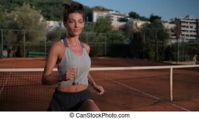 Young woman practicing before a tennis match in the open court.