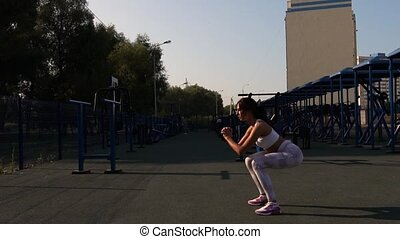Young Woman Practicing Squats in Outdoors Gym