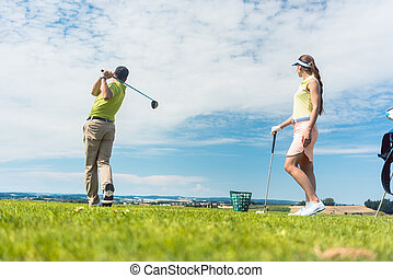 Young woman practicing the correct move during golf class with a