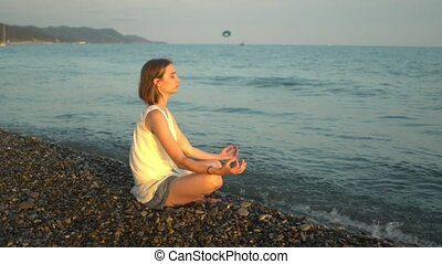 Young woman practicing yoga at the beach. Sunset