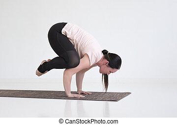 Young woman practicing yoga, doing Crane exercise, Bakasana pose