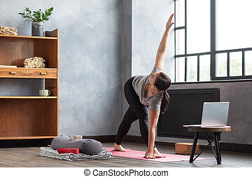 young woman practicing yoga bow pose dhanurasana for