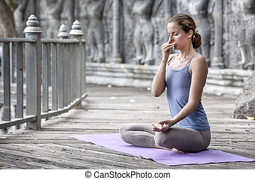 Young woman practicing yoga during yoga retreat in Asia,...
