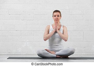 Young woman practicing yoga meditation indoors