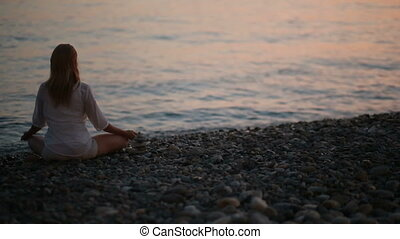 young woman practicing yoga on the beach at sunset. calm sea