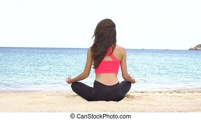 Young woman practicing yoga on the beach at sunset. Exercises calmness and harmony. Meditation in lotus pose. Healthy lifestyle.
