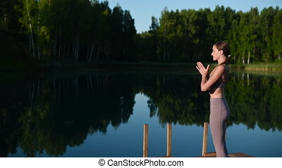Young Woman practicing yoga on the wooden berth at lake. Single sport healthy training on nature at sunny weather.