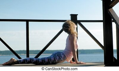 A young woman in yoga performs a greeting to the sun. Surya Namaskar: the eight-point worship of Ashtanga Namaskar, the cobra and the snake represent Bhujangasana on the river bank in the summer at sunrise. Healthy lifestyle