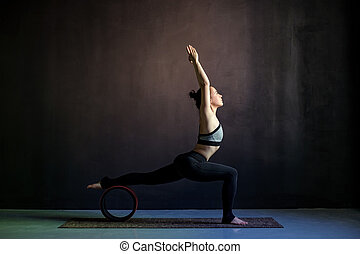 Young woman practicing yoga, standing in Warrior one exercise, Virabhadrasana