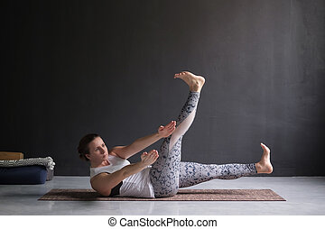 Young woman practicing yoga, stretching in variation of twisted Navasana pose