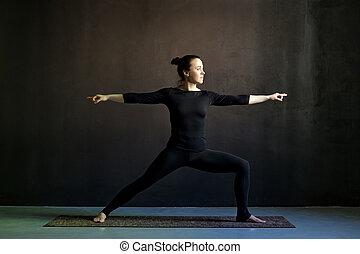 Young woman practicing yoga Warrior pose, Virabhadrasana.
