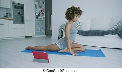 Young woman practicing yoga watching tutoria - Beautiful...
