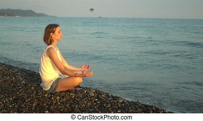 Young woman practises yoga and meditation at the beach. Sunset